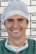 Close up of smiling doctor in front of schedule board in hospital Stock Photos