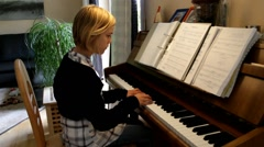Young blonde girl learning to play the home piano. Real sound Stock Footage