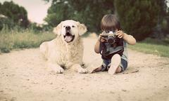 Boy (2-3) with his dog sitting and photographing with old camera Stock Photos