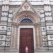 Italia, Tuscany, Siena, Girl (12-13) standing in front of cathedral - stock photo
