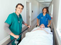 Two doctors pushing patient in bed along hospital corridor Kuvituskuvat