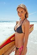 Young woman standing on beach with surfboard underarm - stock photo