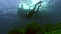 Two scuba divers swimming under dive boat, mediterranean sea Stock Footage
