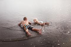 Brothers lying in the shallows Stock Photos