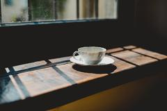 Italia, Lombardia, Pavia, Cup of coffee beside window Stock Photos