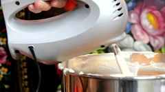 Whipping cream for cake in a bowl by electric hand mixer - stock footage