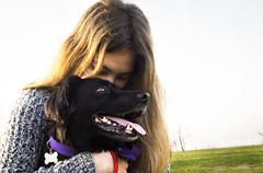 Argentina, Buenos Aires, View of teenage girl (14-15 years) hugging dog Stock Photos