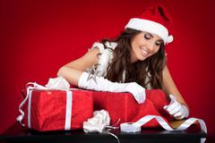 Sexy santas helper wrapping christmas presents Stock Photos