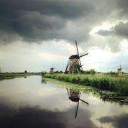 Netherlands, Kinderdijk, Windmills on grassy riverbank Stock Photos