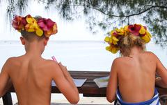 Cook Islands, Rarotonga, Children studying on beach - stock photo