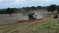 A Combine Harvester Drives Along a Field of Barley Stock Footage