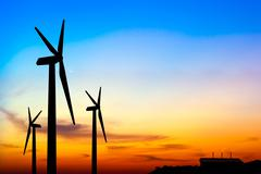 Silhouette wind turbine generator with factory emissions of carbon dioxide Stock Photos