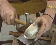 Shaping a silver bowl with an iron hammer Stock Footage