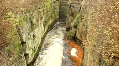 Fast full-flowing foamy water between sandstone rocks, orange sediments Stock Footage