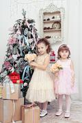 Two girls decorate a christmas tree Stock Photos