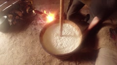 churning fermented sheep's milk wooden gadgets in a wooden barrel and bonfire - stock footage