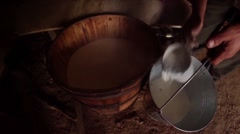 hand pours a glass of milk from a wooden barrel in a pail mountain style - stock footage