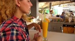 Stock Video Footage of Young Woman Paying Bill while Drinking Fresh Mango Juice at Bar.