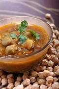indian spicy chana masala, raw chickpeas around bowl - stock photo
