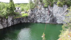 Green lake of inundated marble quarry with alpinism and bungee amusement Stock Footage