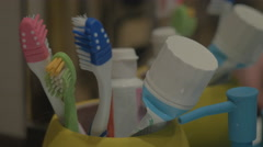 Colorful toothbrushes in a mug Stock Footage