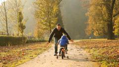 Father and son on the bicycle autumn outdoor - stock footage