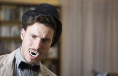 close up young handsome white vampire with black top hat - stock photo
