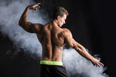 handsome shirtless bodybuilder striking a pose, back view - stock photo