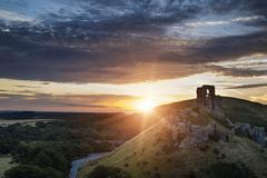 Castle ruins landscape at sunrise with inspirational sunburst behind castle Kuvituskuvat
