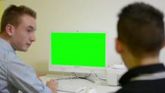Man works on computer - green screen - office - conversation between two man Stock Footage