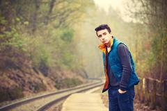 young man is waiting on the platform rural railway station - retro colors - stock photo