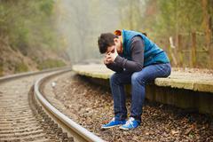 sad young man at the railway station - stock photo