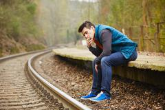 young man is smoking on the platform rural railway station - stock photo