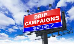Stock Illustration of Drip Campaigns on Red Billboard.