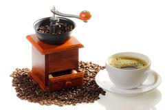cup of coffee and grinding mill with coffee seeds on the white background - stock photo