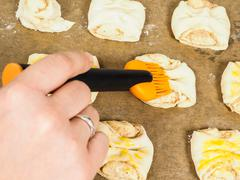 person glazing plaited baked goods with egg wash - stock photo