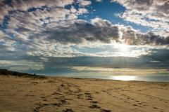 footsteps on sand and dynamic sky over baltic sea - stock photo