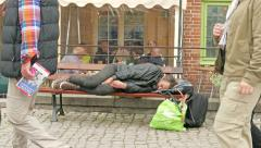 Homeless man sleeps on a bench in the city Stock Footage