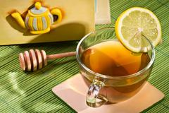 Cup of tea and cupboard with honey dipper Stock Photos