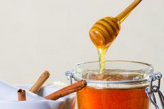 Honey dipper with jar on white background Stock Photos