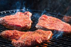 Bbq with fiery steak on the grill Stock Photos