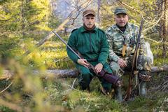 Two older hunters rest Stock Photos