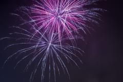 red and blue fireworks during the celebrations at night - stock photo