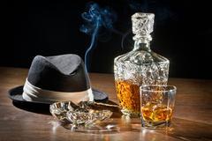 Retro scene, hat, smoking cigar and whisky with carafe Kuvituskuvat
