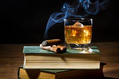 cigar with blue smoke and whisky on ice and two books volume - stock photo
