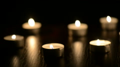 Many small flaming candles on black table Stock Footage