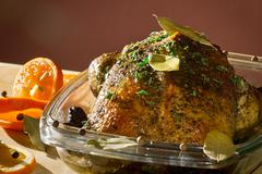 roasted chicken in casserole dish with herbs - stock photo