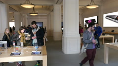 Apple Store interior with people looking at iPhones Stock Footage