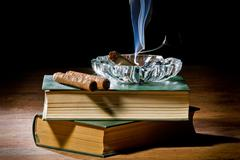 Blue smoke from cigar with ashtray and two books volume Stock Photos