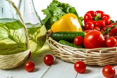 olive oil in a bottle and basket of vegetables - stock photo